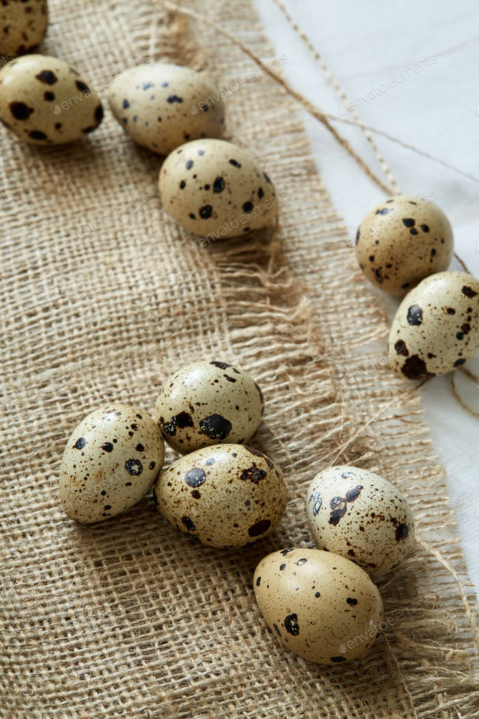 Flatview of some quail eggs on sacloth background