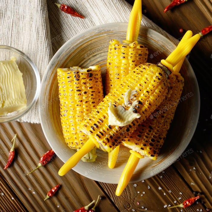 Thumbnail for Top view of Wooden table with deep grilled sweet corn cobs under