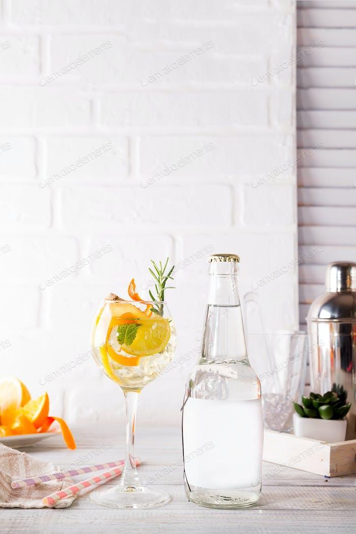 Alkohol Cocktail mit frischen Früchten und Beeren mit einer Flasche Tonic und einem Ort