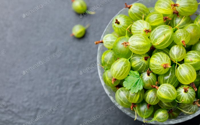 Gooseberries in Glass Bowl on Black Slate Background. Top View. Copy Space.