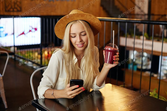 Indoor shot of beautiful stylish long haired blonde woman sitting at table in city cafe