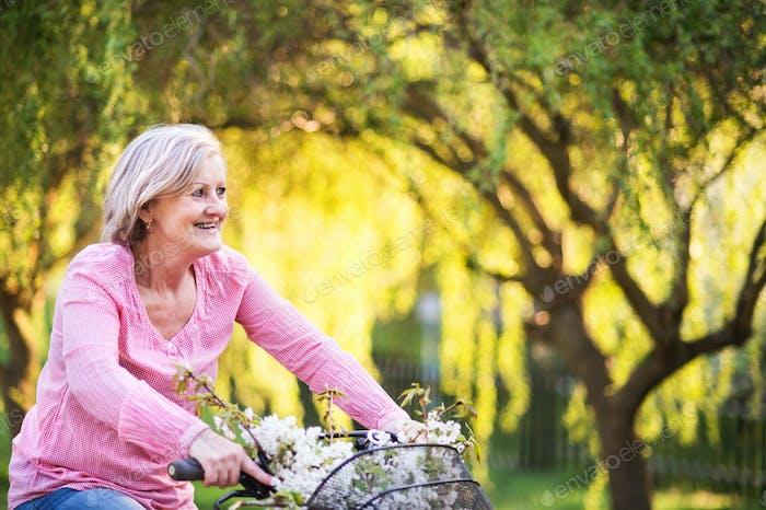 Schöne ältere Frau mit Fahrrad draußen im Frühling Natur.