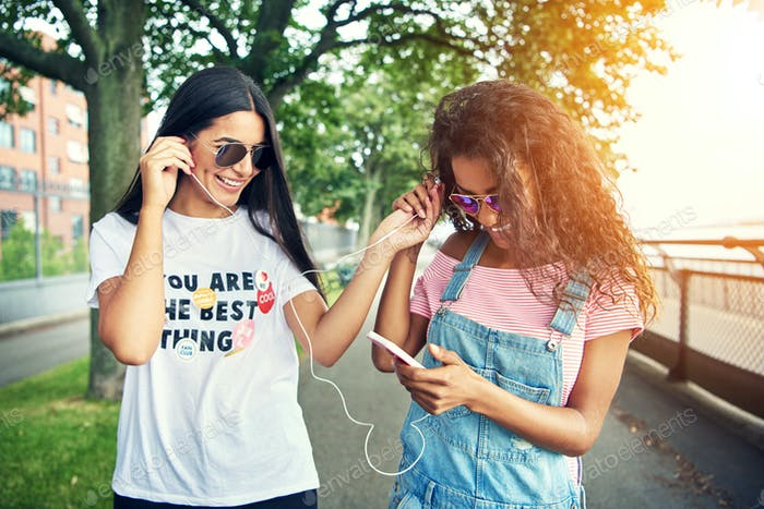Two female friends listen to music on one device