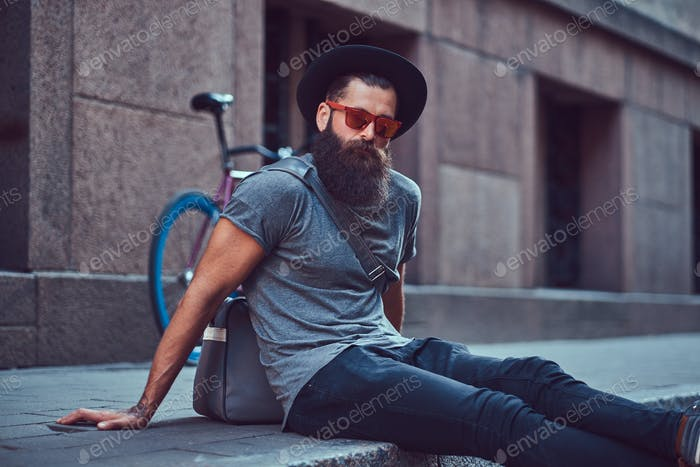 Hipster traveler with a stylish beard and tattoo sits on the sidewalk, resting after a bike ride.