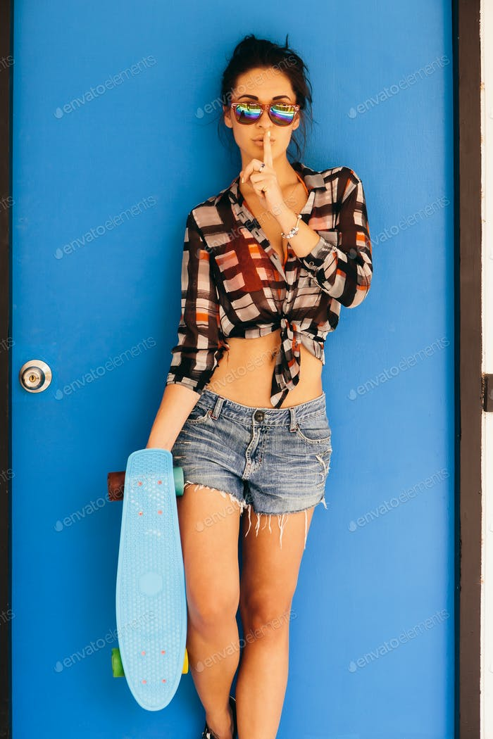 Pretty girl in sunglasses show silence sign.
