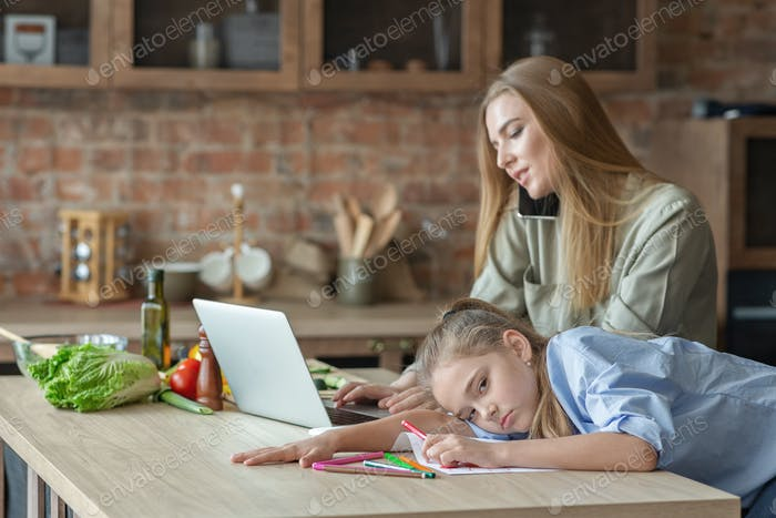 Upset little girl feeling bored while mom working from home