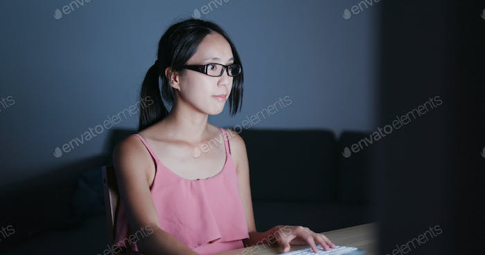 Woman working on computer at night and feeling eye dry