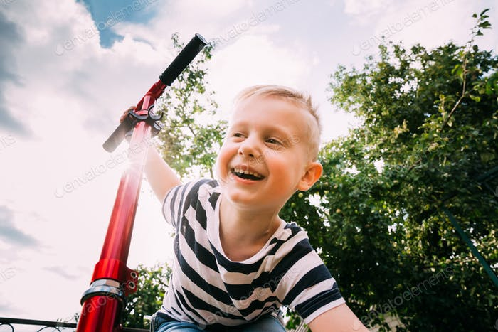 Small Caucasian Baby Boy Having Fun, Smiling And Riding Scooter