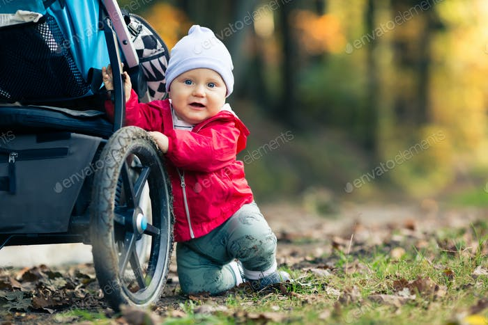 Baby boy playing in autumn forest with stroller, outdoors fun