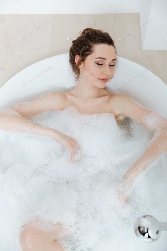 Relaxed pretty young woman lying in bathtub with foam