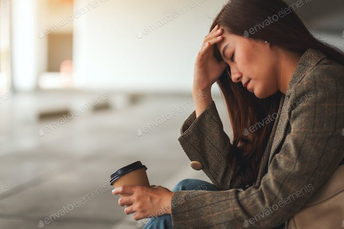 A stressed and headache young asian woman sitting alone
