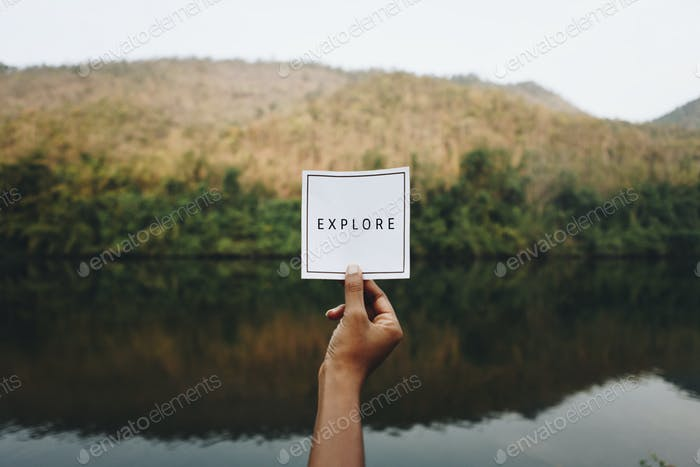 Woman holding up the word explore in nature