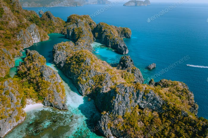 Aerial drone view of a beautiful tropical blue lagoon surrounded by jagged limestone cliffs. Miniloc