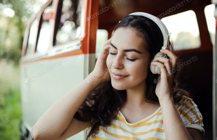 A young girl with headphones on a roadtrip through countryside, listening to music.