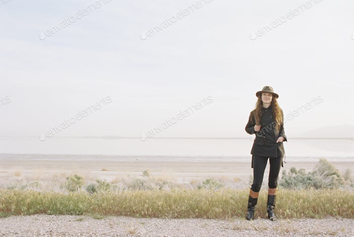 A woman standing on a country road, wearing a hat and carrying a backpack.
