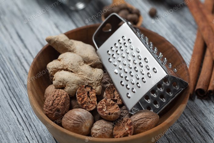 Ginger with nutmeg and grater in bowl on wooden background