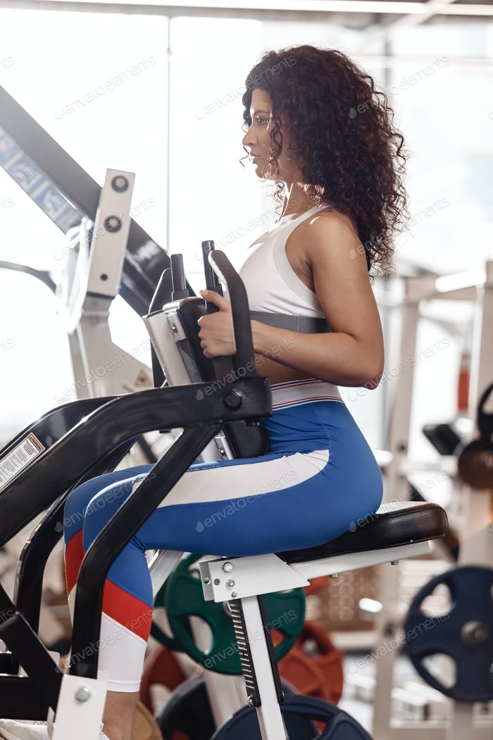 Junge lockig gute Passform Mädchen in Sportkleidung gekleidet tut Übung auf die Sportgeräte in der