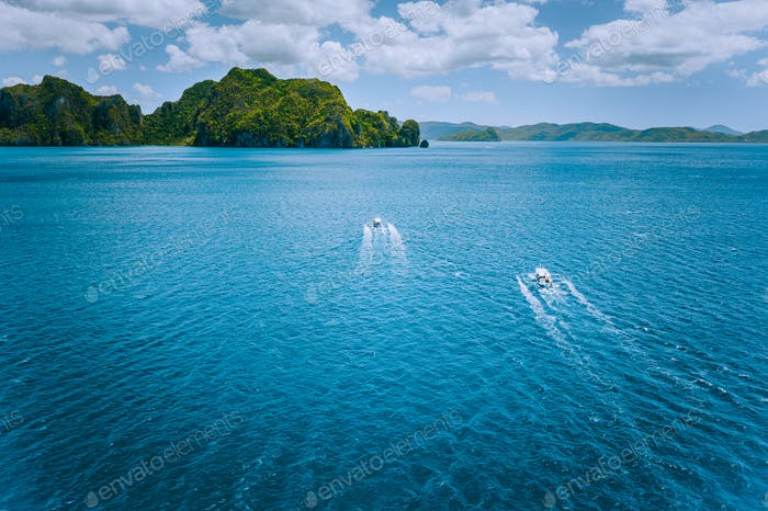 Aerial view of island hopping boats on the way to tour route abound picturesque archipelago. El Nido