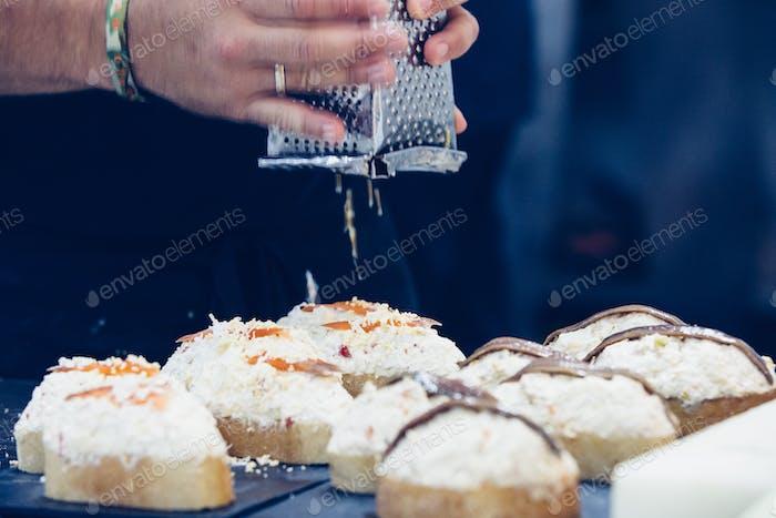 Chef raspelt Ei auf spanischen Tapas