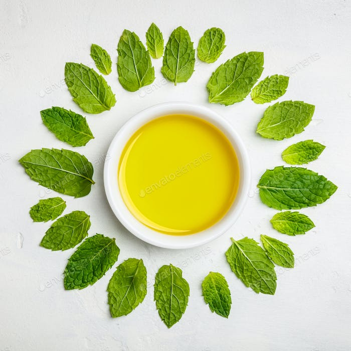 Olive oil and mint leaves on white stone background
