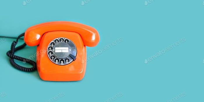 Retro-Telefon orange Farbe, Vintage-Hörer auf grünem Hintergrund. Kopierraum.