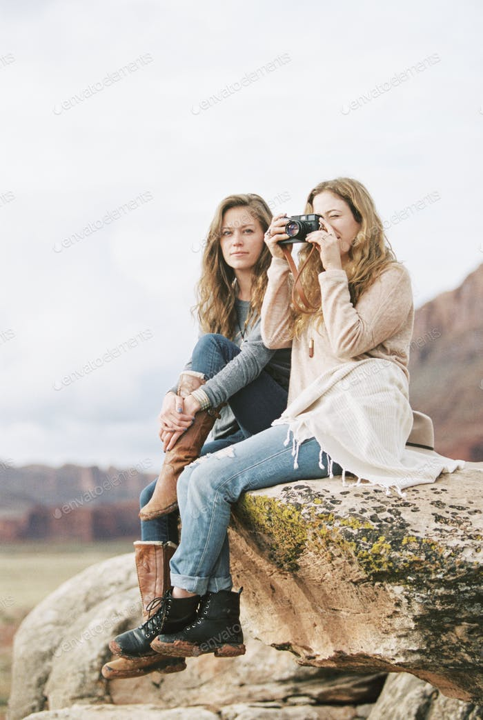 Two women sitting side by side on a rock, one holding a camera.