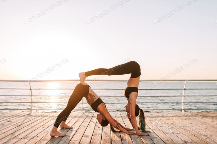 Two young ladies in black sporty tops and leggings standing and training yoga poses by the sea