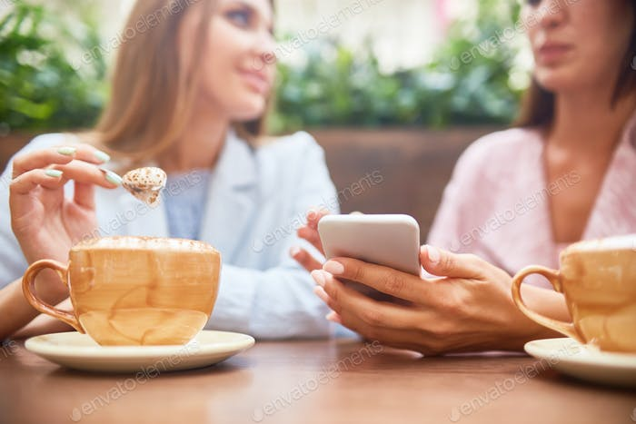 Young Women Using Smartphone in Coffee Shop
