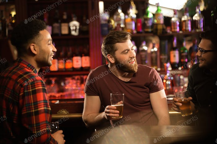 Smiling young men drinking beer