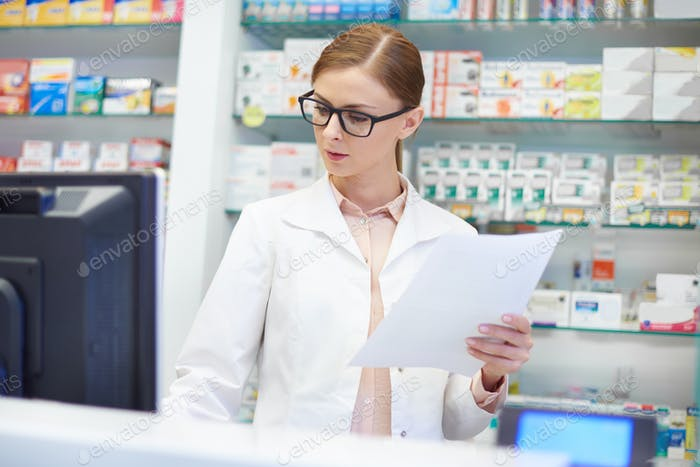 Front view of pharmacist working at drugstore