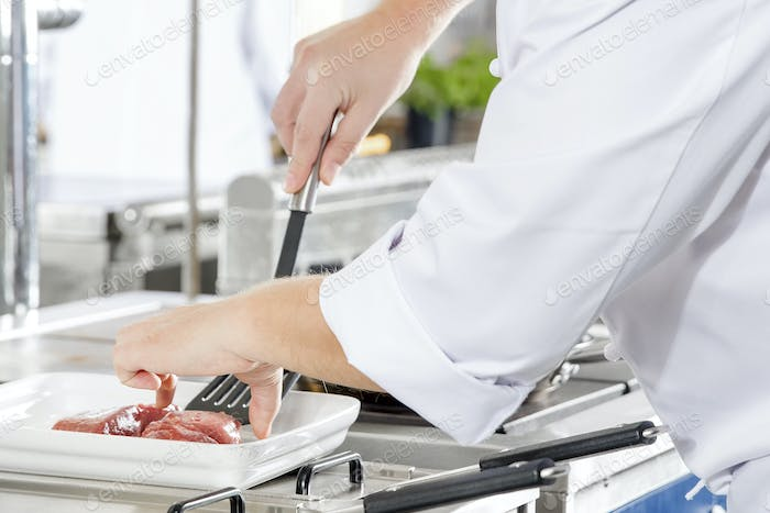 Close-up of a chef prepares beef steak in pan at the kitchen