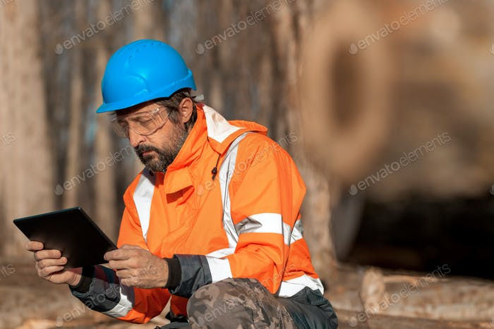 Forestry technician using digital tablet computer in forest