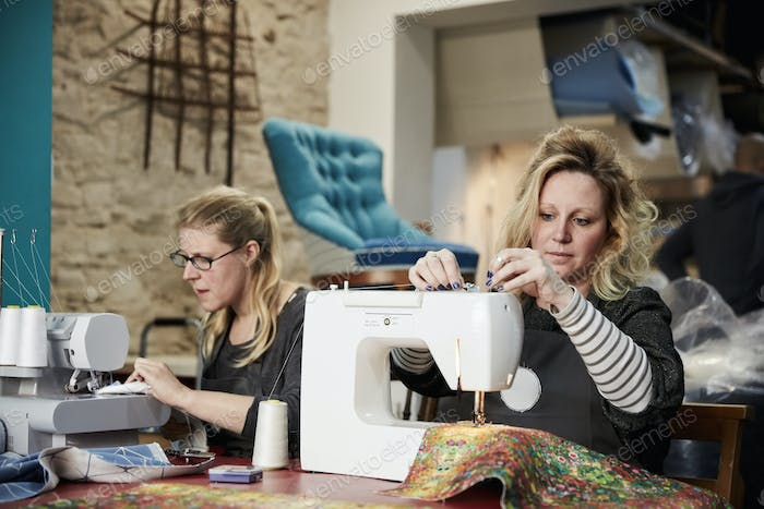 An upholstery workshop. Two women seated using sewing machines.