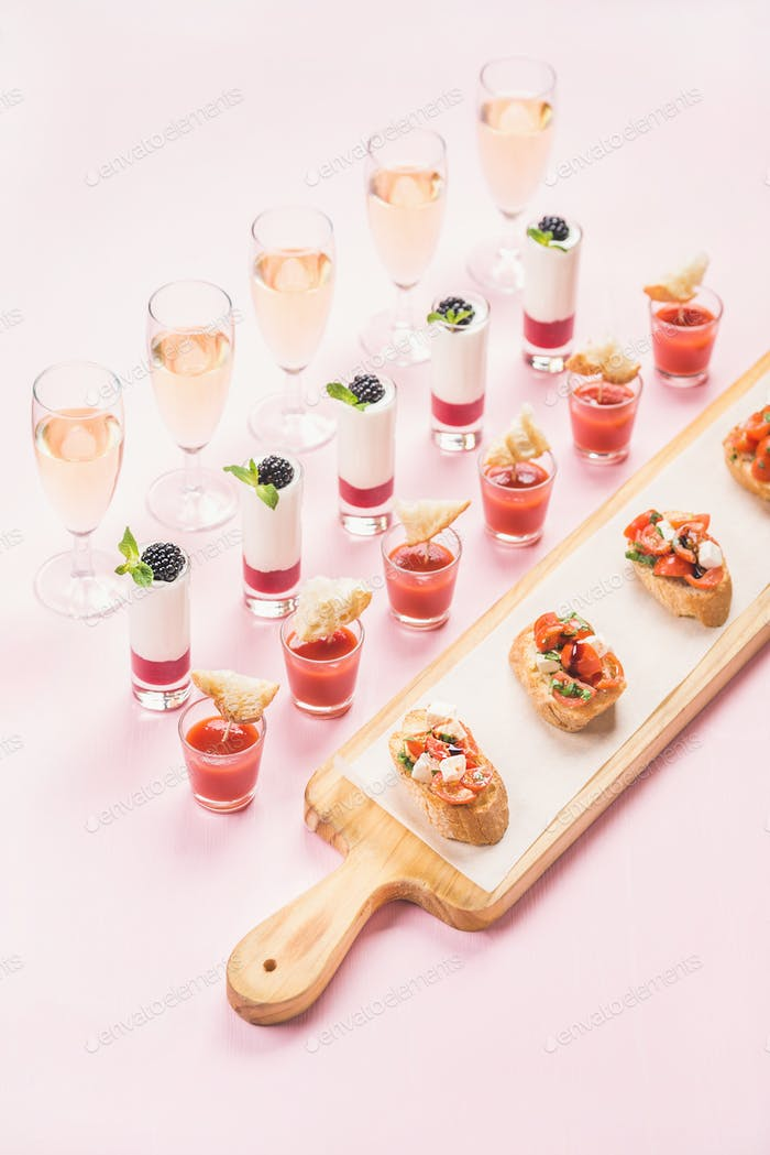 Catering, banquet, party food concept over pastel pink background