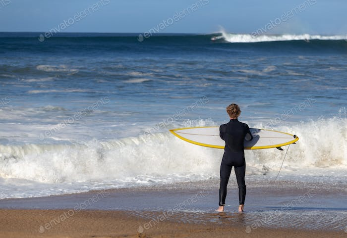 Surfer waiting for wave with yellow board