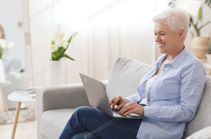 Freelance Jobs For Seniors. Smiling Elderly Lady Working On Laptop At Home