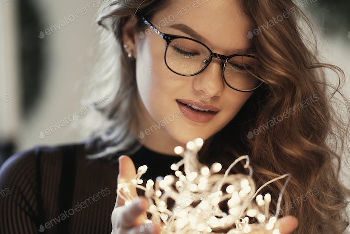 Beautiful woman making a wish while holding lights in her hands