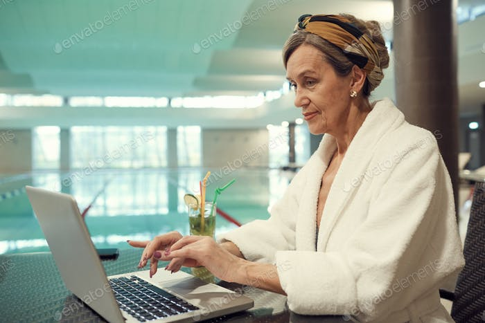 Senior Frau mit Laptop im SPA Resort