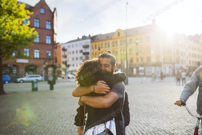 Friends embracing in town square
