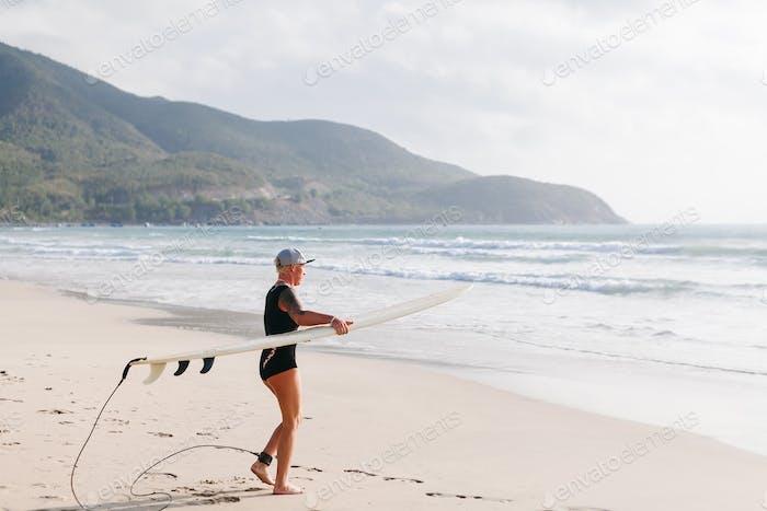 Surffrau mit Surfbrett am Strand