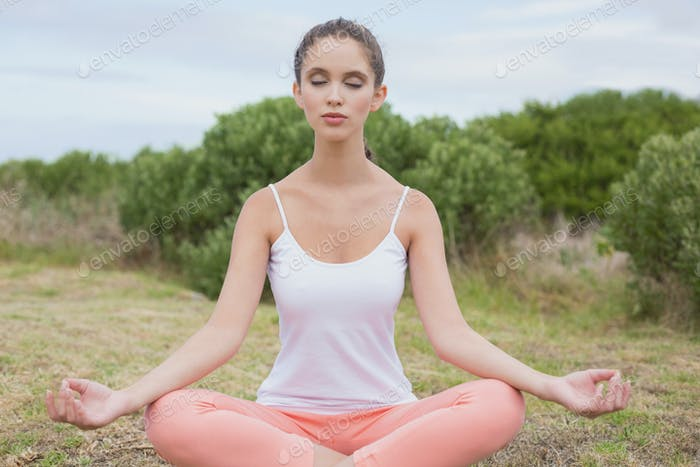 Healthy and beautiful woman sitting in lotus position on countryside landscape