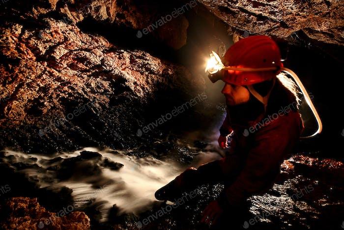 Spelunker erkunden unterirdischen Fluss in einer Höhle