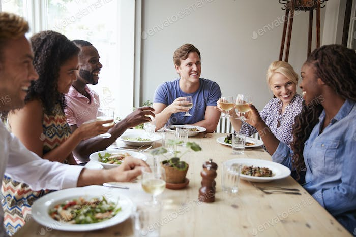 Friends Sitting At Table In Restaurant Making Toast Together