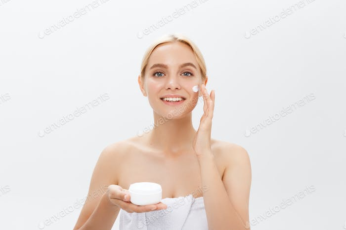 Close up beauty portrait of a laughing beautiful half naked woman applying face cream and looking