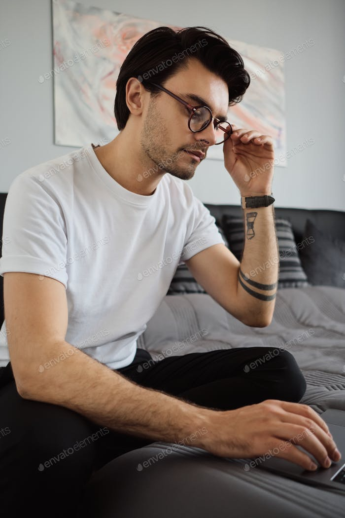Young handsome brunette man in T-shirt and eyeglasses sitting on bed thoughtfully working on laptop