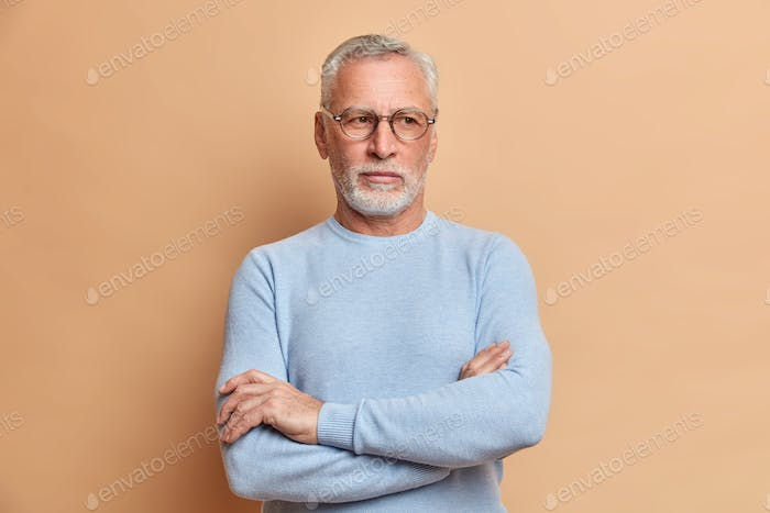 Thoughtful old grey haired grandfather keeps arms folded and looks away pensively ponders over somet