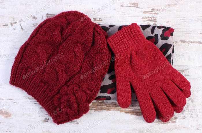 Pair of woolen gloves, cap and shawl for woman on old board