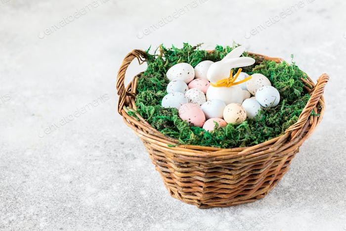 Easter concept.bunny in a basket with easter colored eggs.