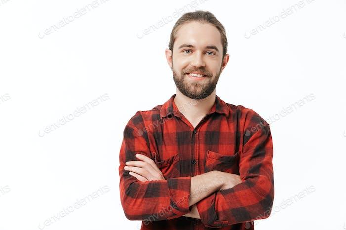 Hombre barbudo posando aislado sobre fondo de pared blanca.