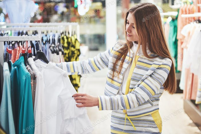 Woman shopping clothes. Shopper looking at clothing indoors in store. Beautiful happy smiling